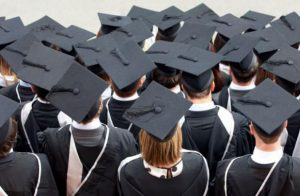 A group of university graduates stands facing away from the camera.